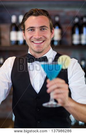 Portrait of happy bartender serving a blue martini in bar