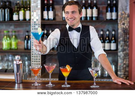 Happy bartender serving a blue martini in bar