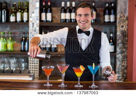 Portrait of bartender pouring a orange martini drink in the glass at bar