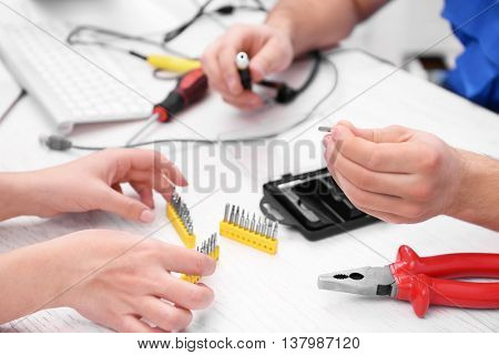 Young repairer with different tips for screwdriver in service center
