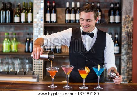 Bartender pouring a orange martini drink in the glass at bar