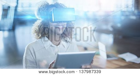 Woman wearing virtual reality glass holding digital tablet in office
