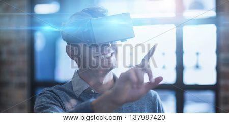 Young businessman gesturing while using virtual reality headset in creative office