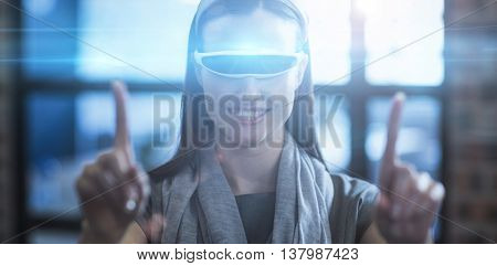 Smiling businesswoman gesturing while using virtual reality headset in creative office