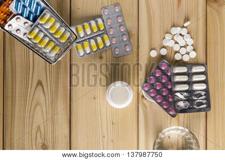 Heap of medicine colorful pills blister pack and water glass