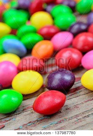 Colorful candies on rustic wooden table closeup