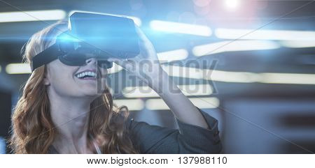 Businesswoman smiling while using virtual reality simulator in office