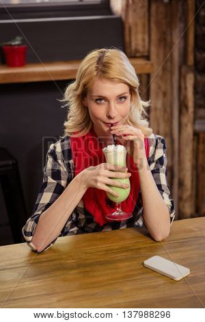 Portrait of beautiful young woman sitting at table drinking mocktail in cafeteria