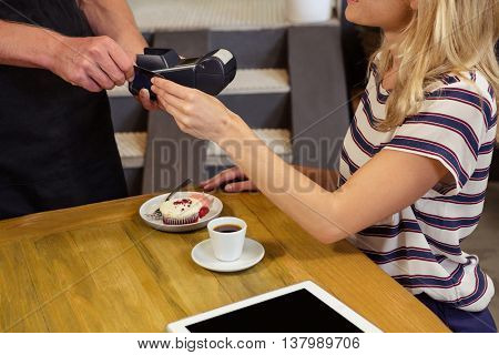 A cashier taking the money to his customer in a coffee