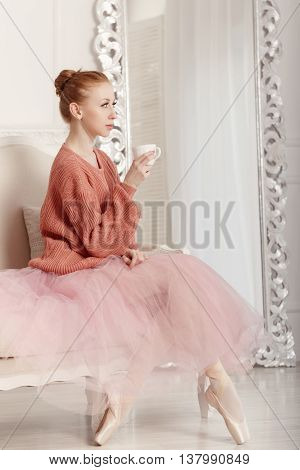 Pretty young ballerina tea drinkers. Ballerina in tutu and pink sweater