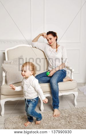 Mother and daughter at home. Baby daughter gives the mother the ball. Girls dressed in white sweaters. Family time