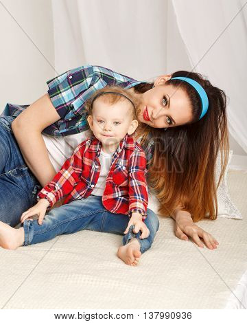 Mother and daughter at home. Young mother and baby daughter hugging. Girls dressed in plaid shirt. Daughter barefoot. Family time