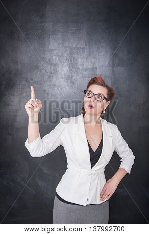 Teacher Showing On Something By Finger On Blackboard Background