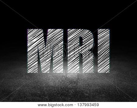 Medicine concept: Glowing text MRI in grunge dark room with Dirty Floor, black background