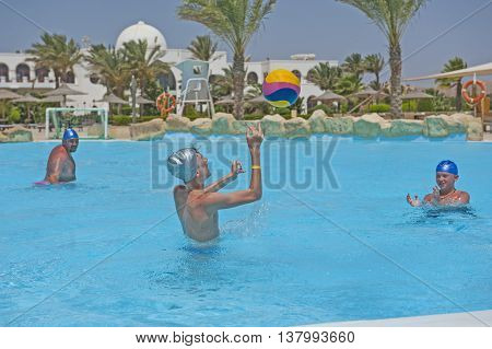 Father And Sons Playing Water In Tropical Resort Pool
