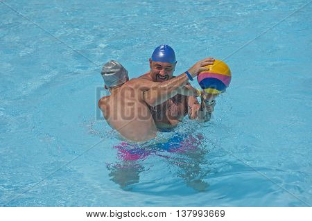 Father and son having fun playing water polo in tropical hotel resort swimming pool on vacation