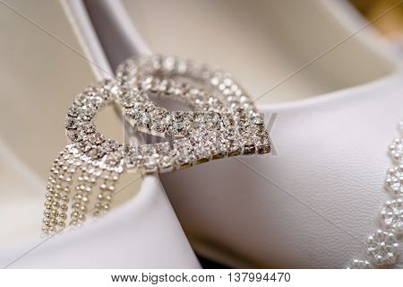 bride bracelet zirconium lies on white shoes.Makro