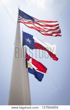DALLAS, TEXAS-MAY 26 2009: The three flags of the United States, State of Texas and City of Dallas fly outside the front of the City Hall building in Dallas, Texas on May 26, 2009.