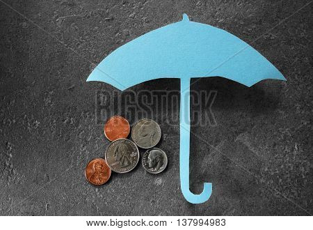 Coins under a paper umbrella -- financial security or retirement savings concept