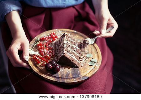 Closeup of woman eating piece of chocolate and fruit cake; wooden plate on her lap