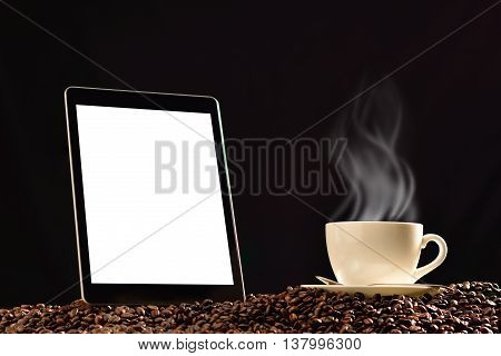 Tablet computer with blank white screen and cup of coffee with smoke on pile of coffee beans