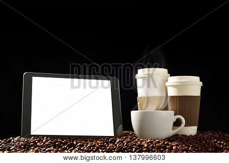 Tablet computer with blank white screen and cups of coffee with smoke on pile of coffee beans