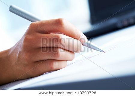 Close-up of business person hand with pen over document