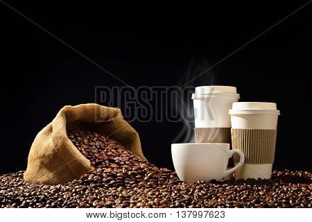 Cups of coffee with smoke and coffee beans in burlap sack on black background