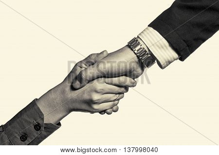 Black and white photo which shows a handshake of two persons isolated and toned