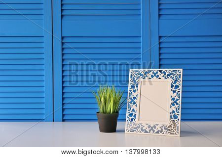 Photo frame with green plant on blue folding screen background