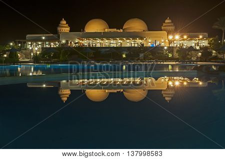 Domed hotel resort building lit up at night with reflection in swimming pool water
