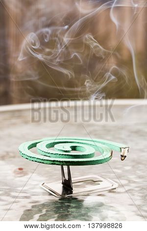 Green Fumigator Over Glass Table