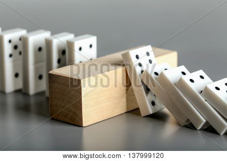 Dominoes and brick block on grey background