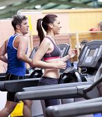 stock photo of treadmill  - Healthy couple running on a treadmill in a sport centre - JPG