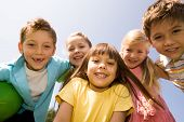 foto of happy kids  - Portrait of happy children embracing each other and laughing with pretty girl in front - JPG