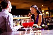 image of flirtatious  - Photo of couple sitting at the table in restaurant - JPG