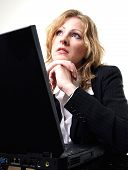Business Woman Looking Up While Sitting At Her Laptop