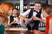 Friends standing at counter while bartender preparing a drink in bar poster