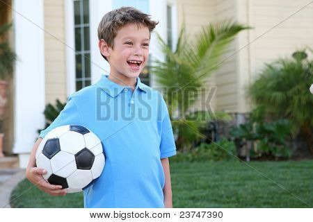 A young boy outside home holding soccer (football) ball