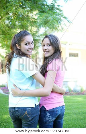 Two attractive hispanic sisters smiling at home