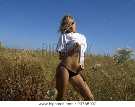 blonde in black bikini in the field
