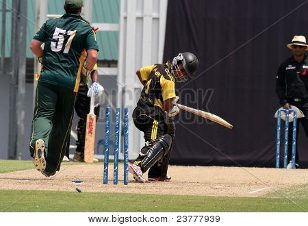 PUCHONG, MALAYSIA - SEPT 24: Guernsey's wicketkeeper T. Kimber hits the stumps as Faris Lee, Malaysia watches at the Pepsi ICC WCL Div 6 finals at the Kinrara Oval, Sept 24, 2011 in Puchong, Malaysia.