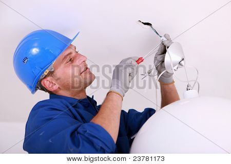 Electrician wiring a ceiling light