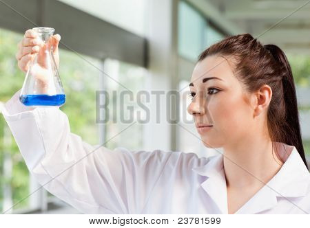 Cute science student looking at a blue liquid in an Erlenmeyer flask