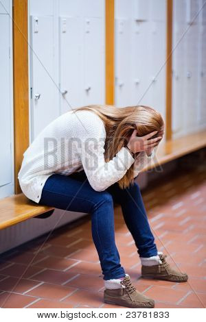 Portrait of a depressed student sitting on a bench in a corridor