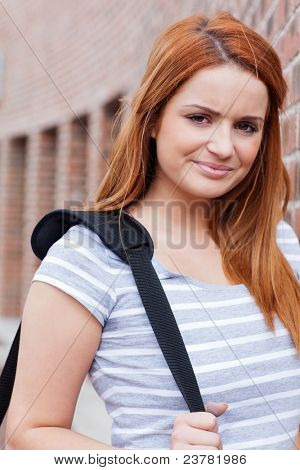 Portrait of a smiling student looking at the camera outside a building