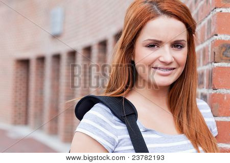 Smiling student looking at the camera outside a building