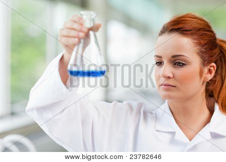 Science student looking at a blue liquid in an Erlenmeyer flask