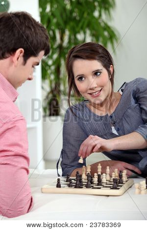 Young couple playing chess.