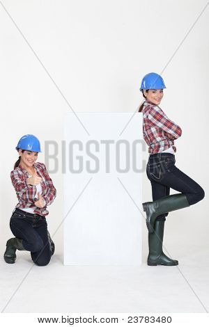 girls wearing blue hard hat striking a pose